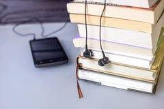 Auriculares en los libros y las notas del vuelo El concepto de audiolibros Foto de archivo libre de regalías