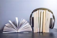 Auriculares en los libros y las notas del vuelo El concepto de audiolibros Fotos de archivo libres de regalías