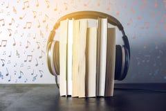 Auriculares en los libros y las notas del vuelo El concepto de audiolibros Foto de archivo
