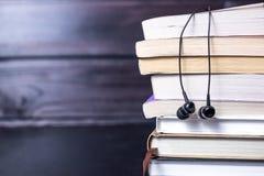 Auriculares en los libros y las notas del vuelo El concepto de audiolibros Fotos de archivo