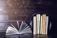 Auriculares en los libros y las notas del vuelo El concepto de audiolibros Fotografía de archivo