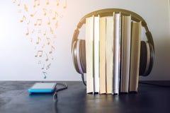 Auriculares en los libros y las notas del vuelo El concepto de audiolibros Fotografía de archivo libre de regalías