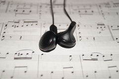 Auriculares en partitura foto de archivo libre de regalías