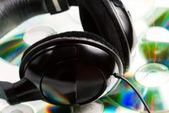 Auriculares encima de los Cdes audios imagen de archivo