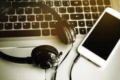 Auriculares estéreos, teléfono móvil y el teclado de un ordenador, música en línea, canción de la transferencia directa en móvil Fotografía de archivo libre de regalías