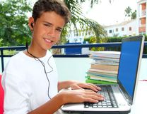Auriculares felices de la computadora portátil del muchacho del estudiante del adolescente Fotografía de archivo libre de regalías