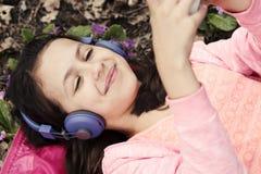 Auriculares felices Violet Smiling de la muchacha Fotos de archivo libres de regalías