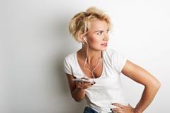 Auriculares femeninos elegantes Smartphone de la música de Blande que escuchan mientras que se opone al fondo blanco Copie el esp Imagen de archivo