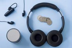 Auriculares inalámbricos, auriculares atadas con alambre, altavoz y monedas fotografía de archivo
