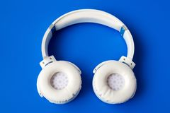 auriculares inalámbricos blancos del bluetooth en fondo azul Foto de archivo libre de regalías
