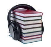 Auriculares llevados en una pila de libros con las cubiertas del color. Fotografía de archivo