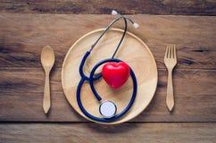 Auriculares médicos puestos en la placa de madera - concepto sano de la consumición imágenes de archivo libres de regalías