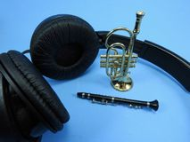 Auriculares negros, un clarinete y una trompeta Los instrumentos musicales son miniaturas imagen de archivo libre de regalías