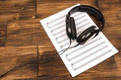Auriculares profesionales negros grandes que mienten en la hoja de música en el fondo de madera Fotos de archivo libres de regalías