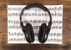 Auriculares profesionales negros grandes que mienten en la hoja de música en el fondo de madera Imagen de archivo