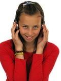 Auriculares que desgastan de la muchacha adolescente linda Foto de archivo libre de regalías
