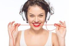 Auriculares que desgastan de la mujer atractiva joven Imagenes de archivo
