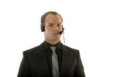 Auriculares que desgastan del hombre de negocios joven acertado Fotografía de archivo