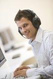 Auriculares que desgastan del hombre en pulsar de la sala de ordenadores Imagen de archivo libre de regalías
