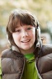 Auriculares que desgastan del muchacho y el escuchar la música Foto de archivo
