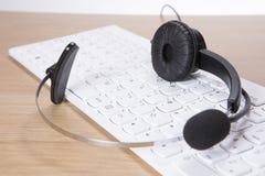 Auriculares que encontram-se em um teclado de computador Fotografia de Stock Royalty Free