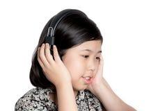 Auriculares que escuchan de la niña Imagenes de archivo