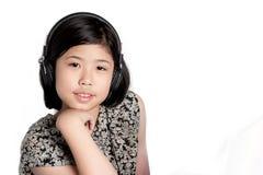 Auriculares que escuchan de la niña Imagen de archivo libre de regalías