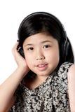 Auriculares que escuchan de la niña Foto de archivo