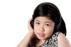 Auriculares que escuchan de la niña Imagen de archivo