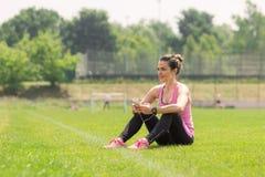 Auriculares que escuchan del teléfono de la hierba de la muchacha del atleta que se sientan Imagen de archivo