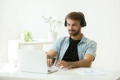 Auriculares que llevan concentrados del trabajador que escuchan webinar en l fotografía de archivo