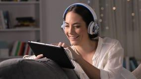 Auriculares que llevan de la muchacha que miran medios en la tableta