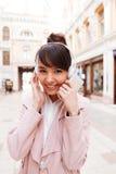 Auriculares que llevan de la muchacha y capa rosada en una calle de la ciudad Imagen de archivo