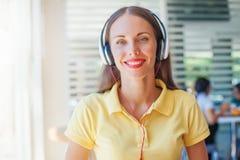 Auriculares que llevan de la mujer de negocios en la oficina Imagen de archivo