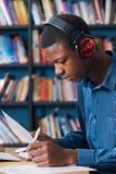 Auriculares que llevan de Working At Computer del estudiante adolescente masculino Foto de archivo libre de regalías