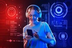 Auriculares que llevan del adolescente feliz y mirada de su smartphone Imagen de archivo libre de regalías