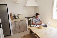 Auriculares que llevan del adolescente usando tecnología en una cocina Foto de archivo libre de regalías