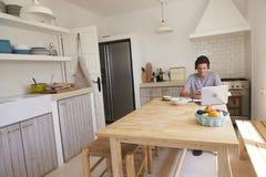 Auriculares que llevan del adolescente usando tecnología en una cocina Imagenes de archivo