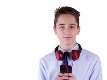 Auriculares que llevan del adolescente y el escuchar la música, comunicando por el teléfono Aislado en el fondo blanco Fotografía de archivo libre de regalías