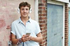 Auriculares que llevan del adolescente y el escuchar la música en S urbano Foto de archivo