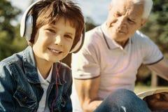 Auriculares que llevan del muchacho feliz y el sentarse con el abuelo Imagen de archivo libre de regalías