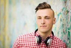 Auriculares que llevan hermosos del hombre joven Fotografía de archivo libre de regalías