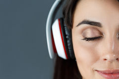 Auriculares que llevan sonrientes cabelludos oscuros hermosos de la mujer Imagen de archivo libre de regalías