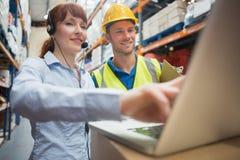 Auriculares que llevan sonrientes de la empresaria usando el ordenador portátil Imagen de archivo
