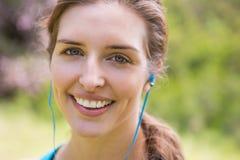 Auriculares que llevan sonrientes de la mujer fotografía de archivo libre de regalías