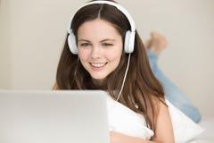 Auriculares que llevan sonrientes de la mujer joven que mienten en cama usando el ordenador portátil Imagenes de archivo
