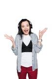 Auriculares que llevan sorprendidos hermosos de la muchacha y mirada de la cámara Fotografía de archivo libre de regalías