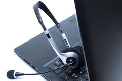 Auriculares que mienten en un teclado de ordenador portátil Fotos de archivo