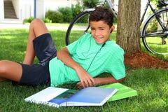 Auriculares sonrientes adolescentes del jardín del libro que estudia del muchacho Imagenes de archivo