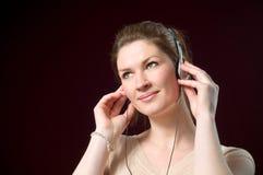 Auriculares sonrientes hermosos de la música de la muchacha que desgastan imagenes de archivo
